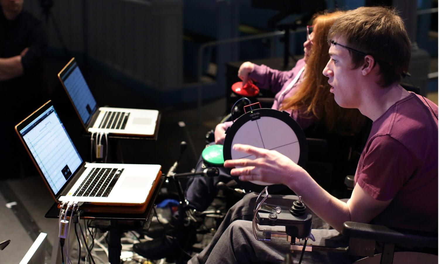 Two disabled performers using digital equipment to take part in the Digital Orchestra at Drake Music Scotland. Image by Anne Binckebanck