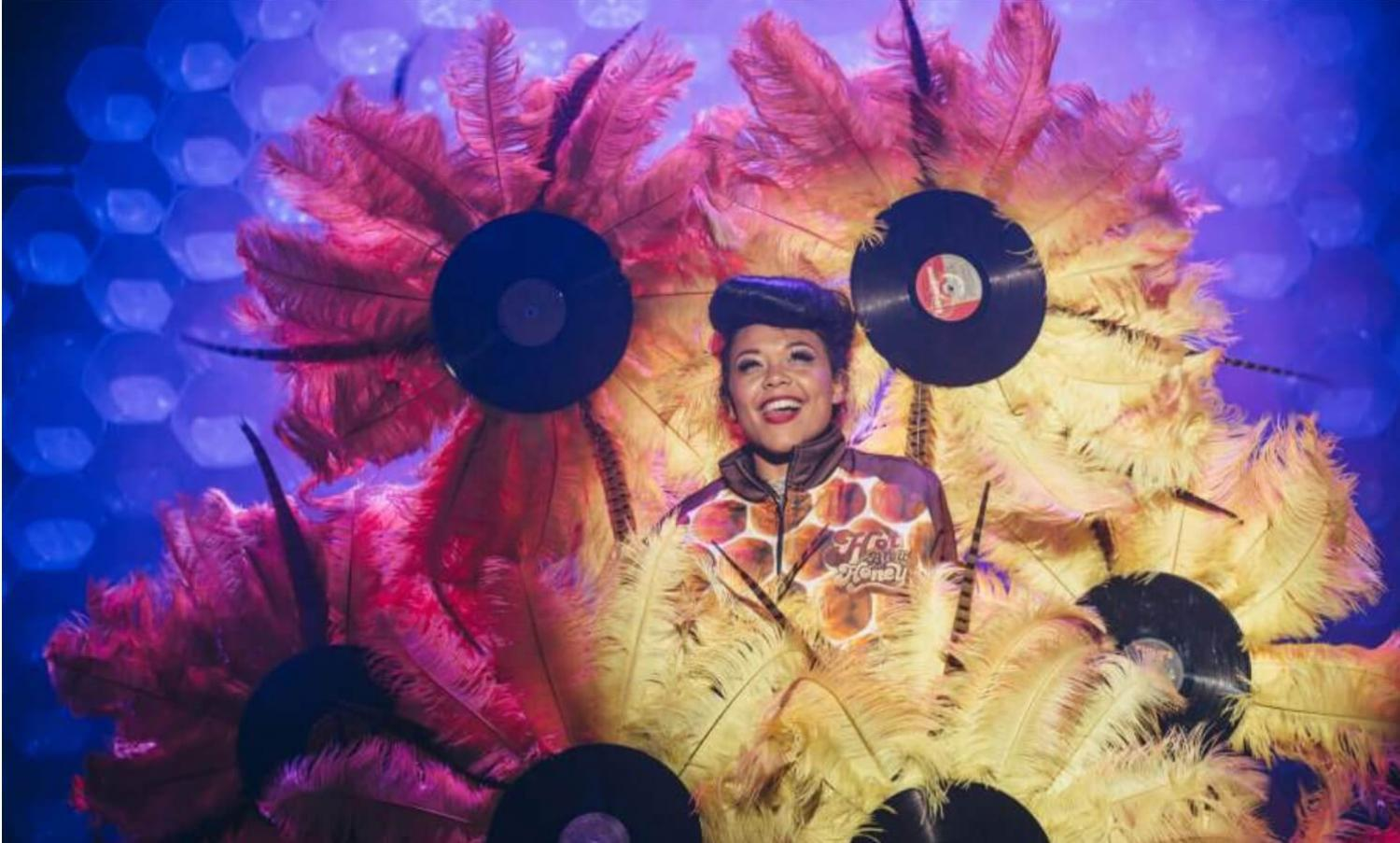 Hot Brown Honey on stage at a Fringe venue surrounded by large feathers and records made to look like flowers. Image by: David Monteith Hodge