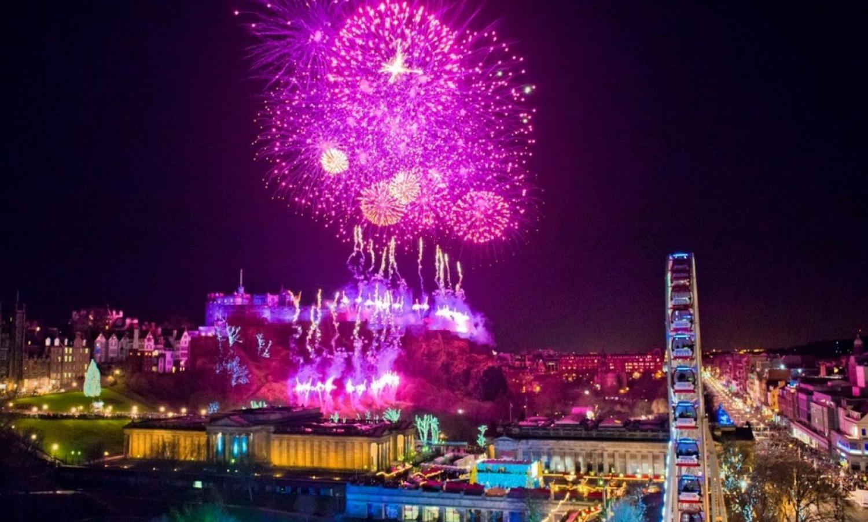 Purple fireworks above Edinburgh Castle and Big Wheel at Edinburgh's Hogmanay