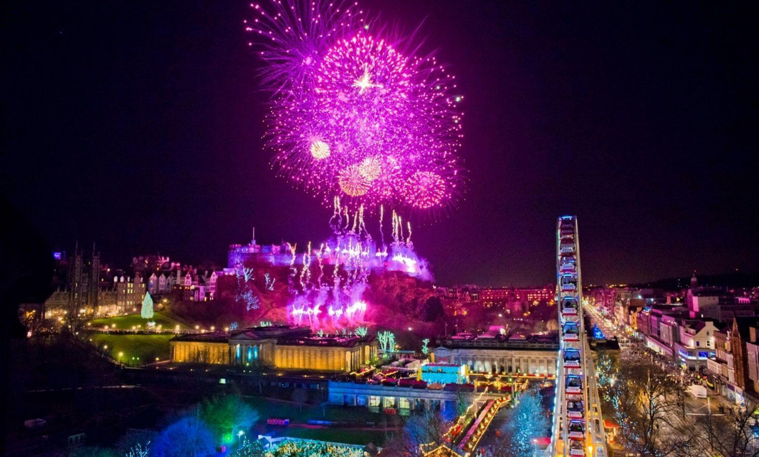 Hogmanay fireworks over Edinburgh Castle and the Big Wheel in Princes Street Gardens.