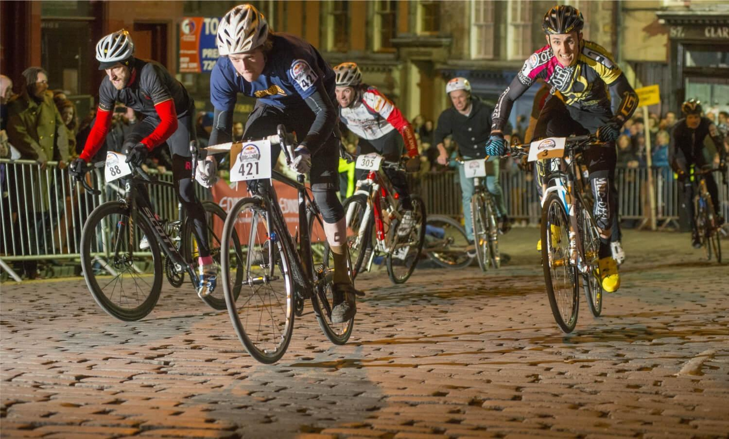 Five participants of Red Bull Hill Chasers event cycling up a cobbled street in Edinburgh with spectators on either side of the road behind metal barriers.