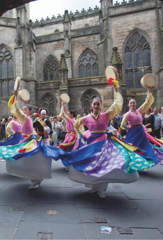 Five dancers in full skirts and with tambourines perform for a crowd on the Royal Mile at the Edinburgh Festival Fringe