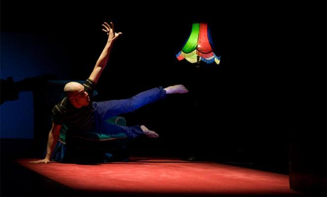Award Recipient Tony Mills in Watch iT! leaping over props on black stage with a colourful lamp in the background